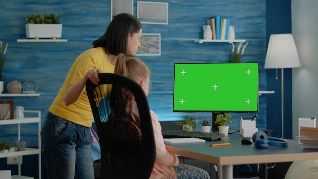 水平方向の緑色の画面で宿題をしている母と生徒