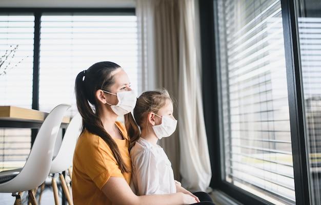 집에서 안면 마스크를 쓴 엄마와 어린 아이가 밖을 내다보고 있습니다. 코로나 바이러스와 검역 개념.