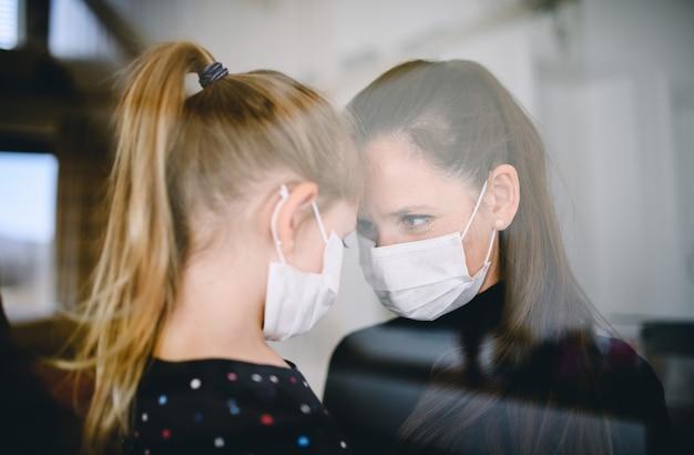 집에서 안면 마스크를 쓴 엄마와 어린 아이가 이야기를 하고 있다