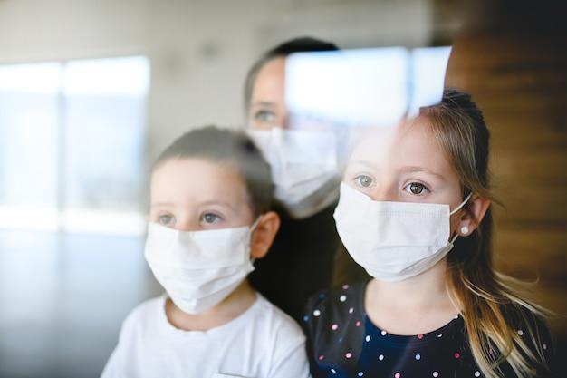 집에서 안면 마스크를 쓴 엄마와 어린 아이들이 밖을 내다보고 있다