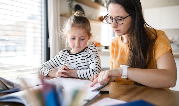 집에서 실내에서 배우는 엄마와 작은 딸, 코로나 바이러스, 검역 개념.