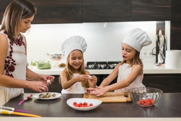 Мать и улыбающаяся милая дочь, чистящая вареные перепелиные яйца на кухонной рабочей поверхности