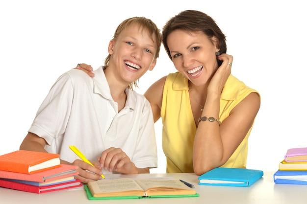 Мать и сын вместе рисуют карандашами за столом