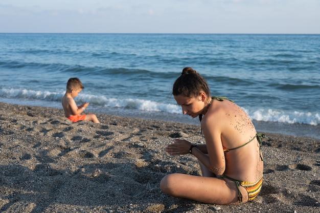 엄마와 아들은 바다 근처에서 놀고 있습니다. 엄마와 아이는 일몰 동안 해변에서 함께 시간을 보냅니다.