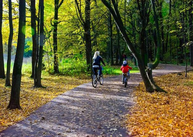Мать и сын катаются на велосипедах в осеннем парке обратно к камере