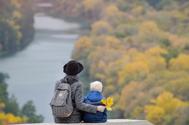 Мать и сын сидят на возвышенности. осень. река и лес внизу. вид сзади
