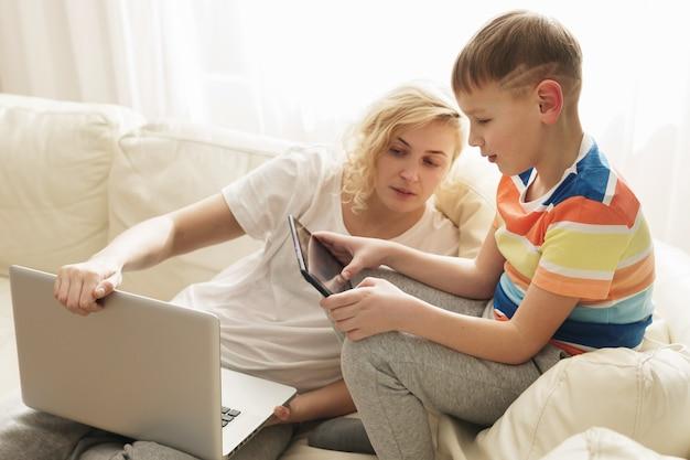 家にいる母と息子。少年はタブレットpcの使い方を学んでいます。