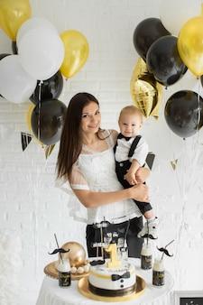 Мать и сын празднуют 1-й день рождения вместе смеяться и улыбаться с воздушными шарами, моноблок.