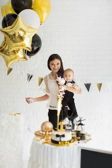1歳の誕生日を祝う母と息子が一緒に風船、キャンディーバーで笑ったり笑ったりします。