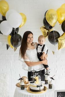 함께 웃고 풍선으로 웃고있는 1 번째 생일을 축하하는 어머니와 아들