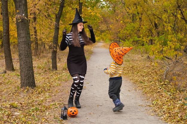 가을 숲에서 할로윈 의상을 입고 춤을 추는 엄마와 아들