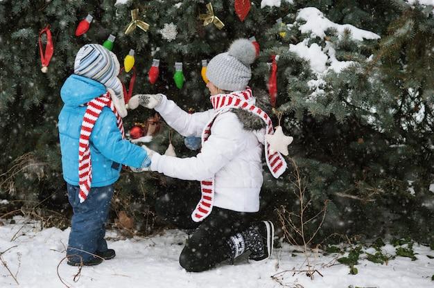 Мать и сын украшают елку на улице в зимнем парке,