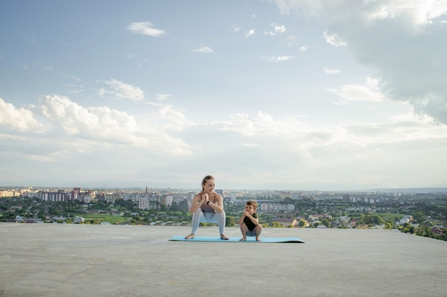 健康的なライフスタイルのコンセプトである日の出や日没の間に都市の背景にあるバルコニーで運動をしている母と息子。
