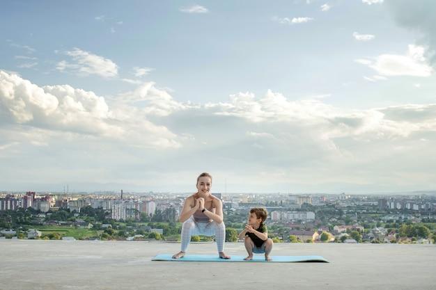 Мать и сын делают упражнения на балконе на фоне города во время восхода или заката, концепция здорового образа жизни.