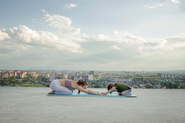 Мать и сын делают зарядку на балконе в городской стене во время восхода или заката