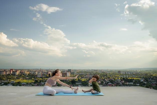 健康的なライフスタイルの日の出や日没のコンセプトの間に、街のバルコニーで運動する母と息子