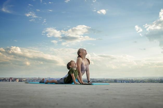 Мать и сын делают упражнения на балконе