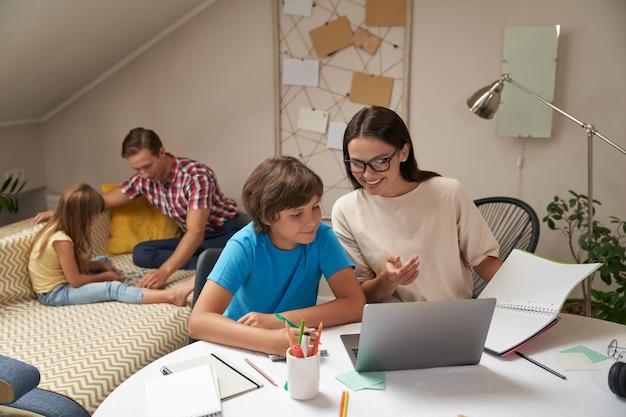 아버지와 딸이 소파에 앉아서 노는 동안 어머니와 아들이 함께 학교 숙제를 하고 있다