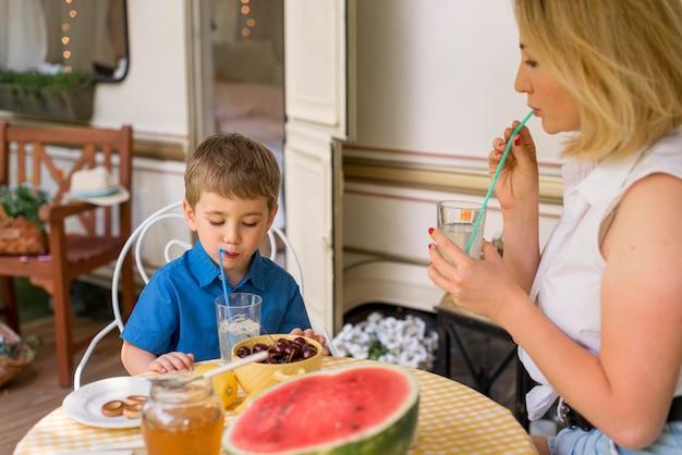 母と息子が外でレモネードを飲む