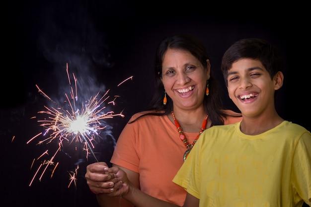 ディワリ祭のお祝いの一環として、きらめく花火を楽しむ母と息子