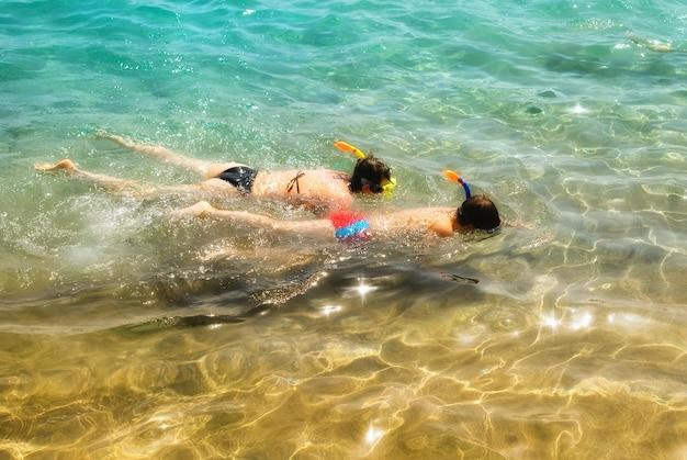 Семья матери и сына, подводное плавание в бирюзовом море
