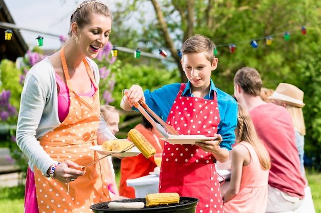 庭のバーベキューで肉を焼く母と息子