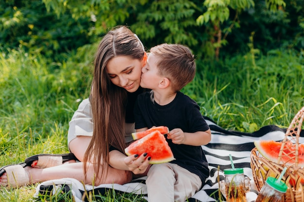 어머니와 아들이 공원에서 피크닉을 데 수 박 조각을 들고있다. 아들이 어머니를 키스