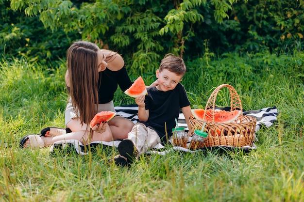 어머니와 아들이 공원에서 피크닉을 데 수 박 조각을 들고있다.