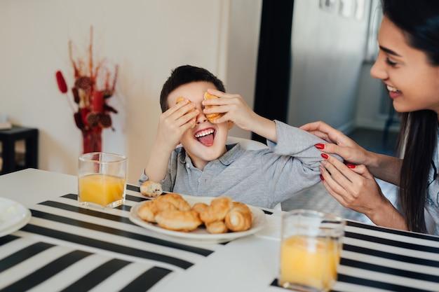 母と息子は楽しんでいます。キッチンで家族の朝食