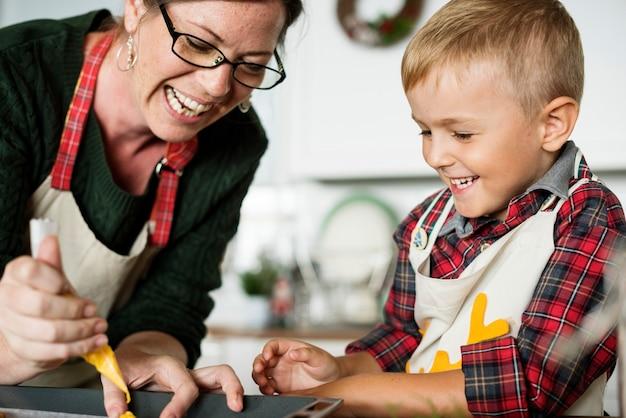 キッチンで楽しんでいる母と息子