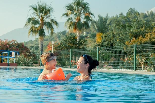 水で遊ぶ女性と子供を泳ぐことを学ぶ屋外プールの子供で母と息子家族の夏休み子供のためのアクティブで健康的なスポーツ