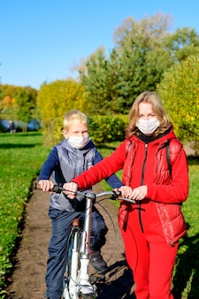 医療用マスクの秋の公園の前景にいる母と息子。
