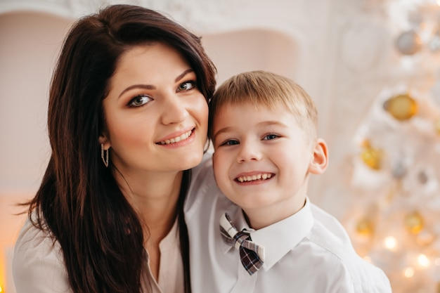 スタジオクリスマスの母と息子。クリスマスツリーの近くに座っている幸せな母と幼い息子の肖像画。