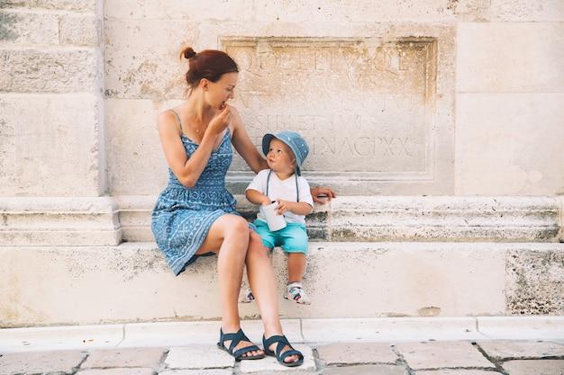 크로아티아 자다르의 엄마와 아들. 유럽 해안의 여름 휴가. 자다르의 오래된 역사적 거리를 걷고 있는 관광객들. 라이프 스타일, 가족, 휴가 및 여행 개념.