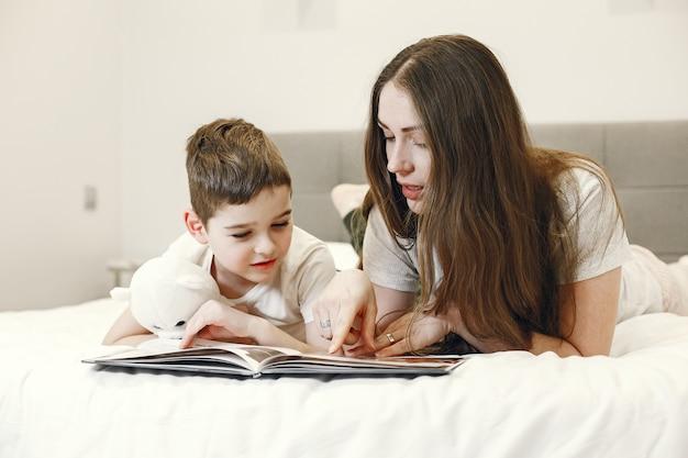 Мать и сын, лежа на кровати, читают книгу.