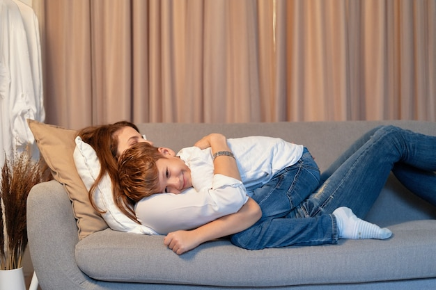 母と息子がソファに横になって抱き合って、怠惰な日、ママと子供の瞬間