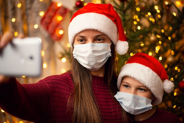 Мать и сын делают селфи возле елки, оба в новогодних шапках и медицинских масках.