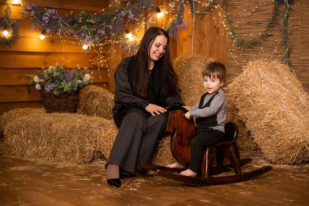 母と息子のわらの束とファームバックグラウンドでロッキングホース