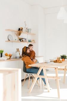 Мать и сын на стуле обнимаются