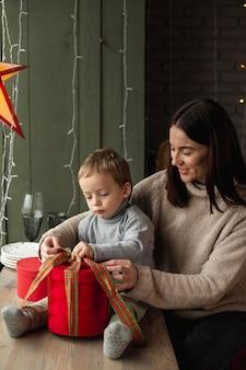 母と息子がクリスマスプレゼントを開く
