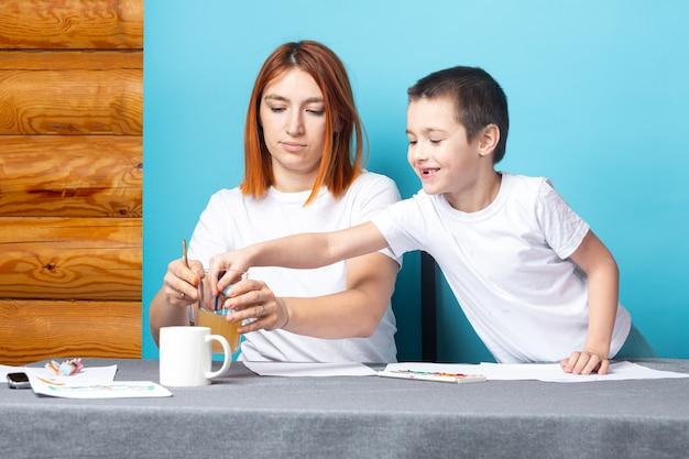 Мать и сын рисуют на синей поверхности