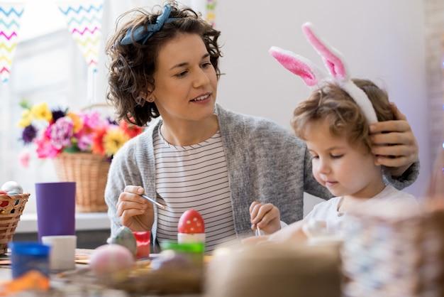 母と息子のイースターエッグを塗る