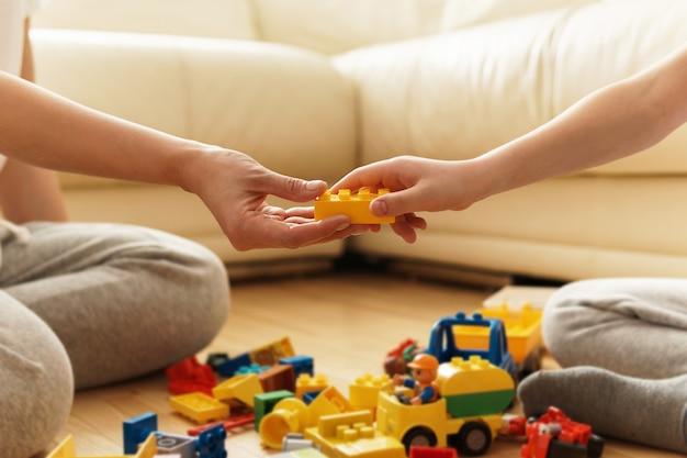 Мать и сын играют дома с игрушками cunstrction