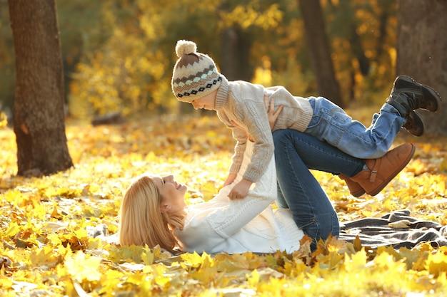 美しい秋の公園で遊ぶ母と息子