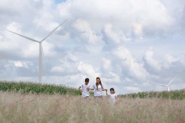 Мать и сын играют в поле с огромной ветряной турбиной в фоновом режиме