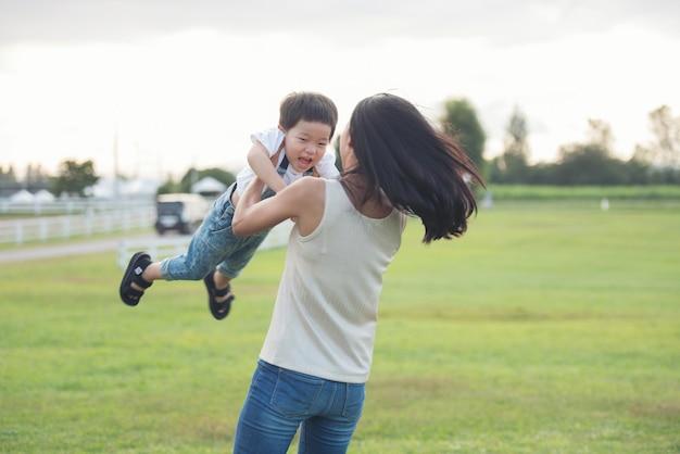 日没時に公園で遊ぶ母と息子。フィールドで楽しむ人々。フレンドリーな家族と夏休みのコンセプト。息子を宙に放り投げる母親。