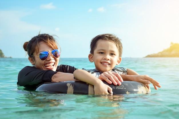 海で遊んで週末に楽しく笑う母と息子