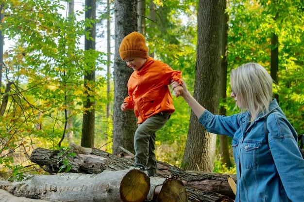 숲에서 통나무를 가지고 노는 엄마와 아들