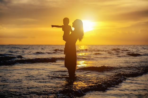 夕日にビーチで遊んでいる母と息子。フレンドリーな家族の概念。