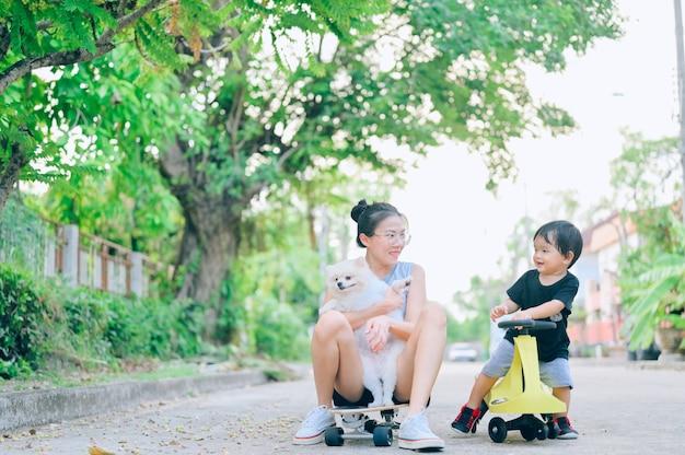 Мать и сын играют на дороге в дневное время со щенком померанского шпица. понятие дружной семьи.